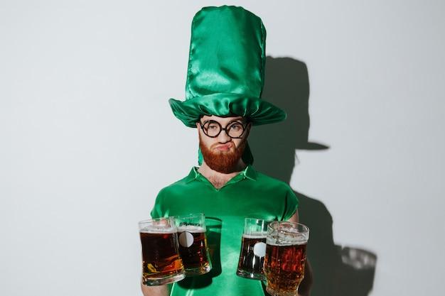 Homem descontente em traje de st.patriks segurando muitos copos