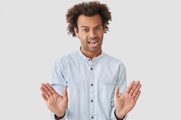 Homem descontente faz gesto de parar com expressão irritante, pede para não incomodar, rejeita algo, aperta as palmas das mãos, tem cabelo crespo