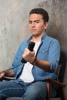 Homem descontente, segurando o monofone e sentado na cadeira. foto de alta qualidade