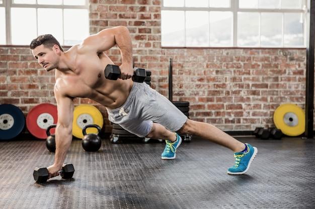 Homem descontraído que se exercita com halteres