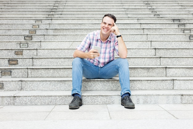 Homem descontraído que usa o smartphone na escadaria da cidade