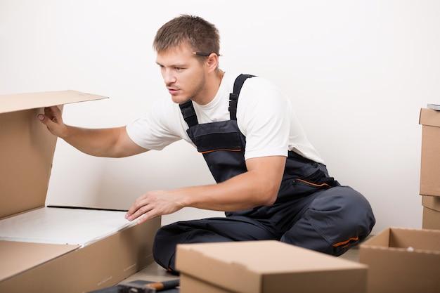 Homem desempacotando coisas após se mudar para a nova casa. diy, nova casa e conceito de mudança