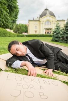 Homem desempregado frustrante com sinal deitado no gramado.