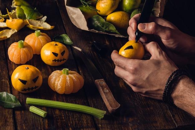 Homem desenhando rostos de halloween em tangerinas