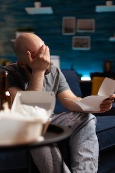 Homem desesperado, deprimido e frustrado lendo carta de papel do locatário com contas bancárias