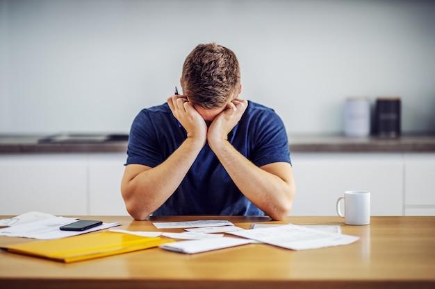 Homem desesperado encostado na mesa e segurando a cabeça nas mãos porque não tem dinheiro para pagar as contas.