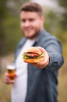 Homem desfocado com tiro médio segurando hambúrguer
