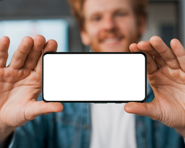 Homem desfocado segurando um celular do espaço da cópia
