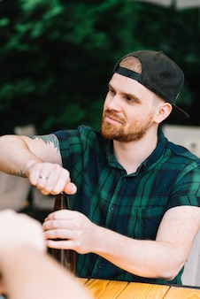 Homem, desgastar, boné, abertura, a, garrafa cerveja
