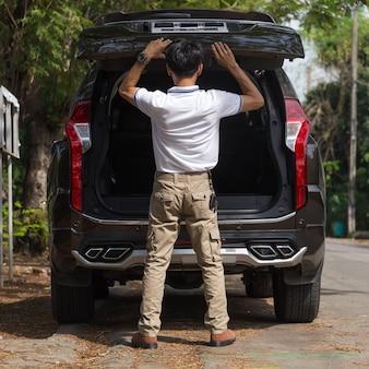 Homem, desgastar, carga, calças, com, suv, estacionamento carro, em, a, natureza, parque
