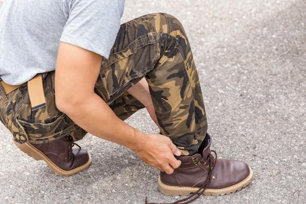Homem, desgastar, carga, calças, e, amarrando, a, laços, ligado, couro, sapatos, botina