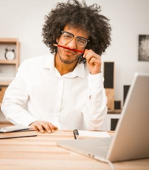 Homem desgrenhado faz careta, olhando para a câmera e segurando o lápis no nariz como bigode. jovem árabe trabalhar ou estudar em casa. imagem enfraquecida