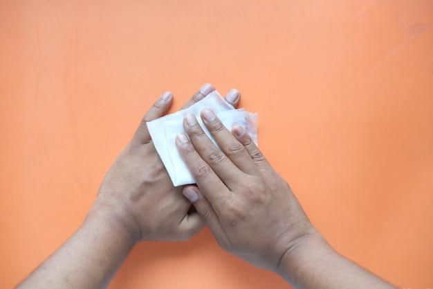 Homem desinfetando as mãos com um pano úmido