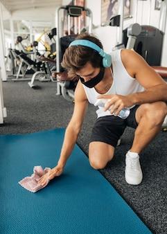 Homem desinfetando tapete na academia