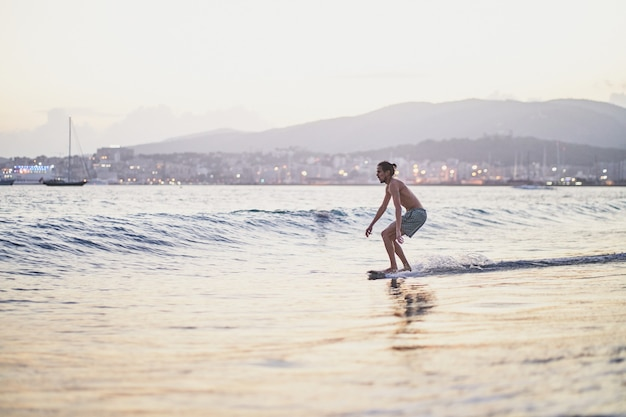 Homem deslizando com seu skimboard para se aproximar de uma onda na praia durante o pôr do sol