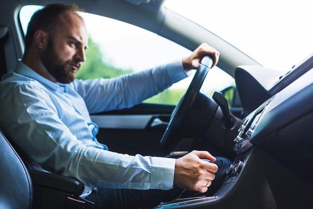 Homem, deslocando, vara engrenagem, enquanto, dirigindo carro