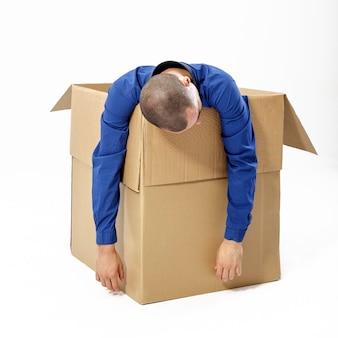 Homem desmaiado em uma caixa de papelão em um fundo branco