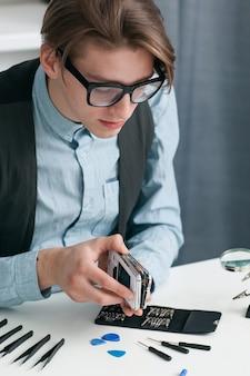 Homem desmontando smartphone na oficina.