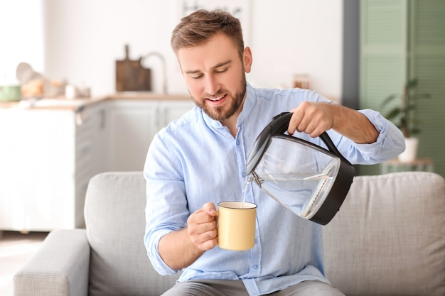 Homem despejando água quente fervida de uma chaleira elétrica em um copo em casa