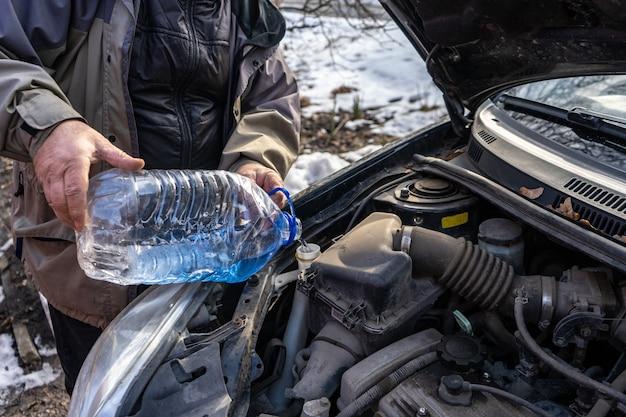 Homem despejando anticongelante em tanque de fluido especial