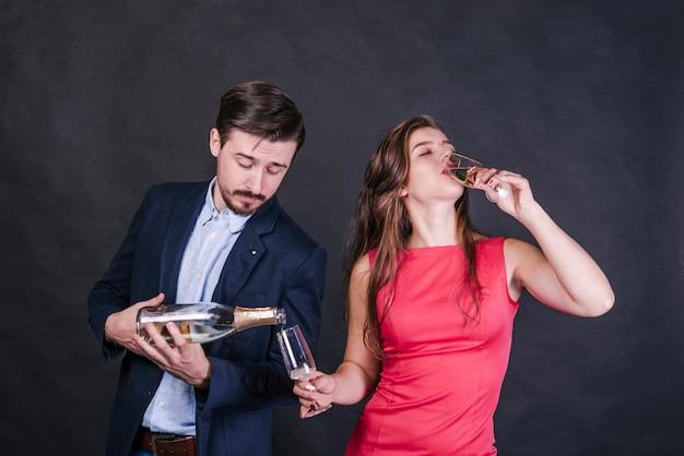 Homem, despejar, champanhe, em, vidro, enquanto, mulher, bebendo