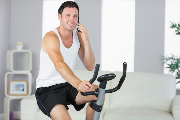 Homem desportivo alegre exercitando em bicicleta e telefonando