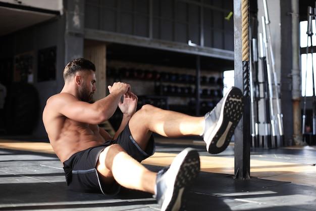 Homem desportivo, alongamento e aquecimento, fazendo exercícios especiais para os músculos antes de trabalhar o corpo.