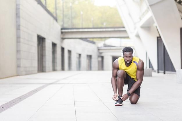 Homem desportivo amarra os cadarços dos tênis antes de correr. tiro ao ar livre, de manhã. primavera ou verão