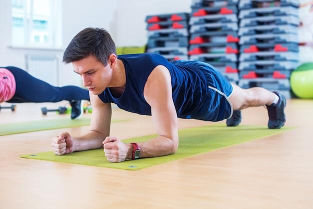 Homem desportivo atlético de treinamento fitness fazendo exercício de prancha na aula de ginástica ou ioga, exercício de treino