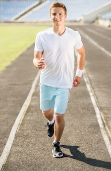 Homem desportivo bonito correndo ao ar livre ao nascer do sol.