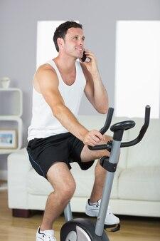 Homem desportivo bonito exercitar na bicicleta e telefonar