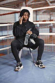 Homem desportivo boxe. foto de boxeador em um anel. homem afro-americano treinando.
