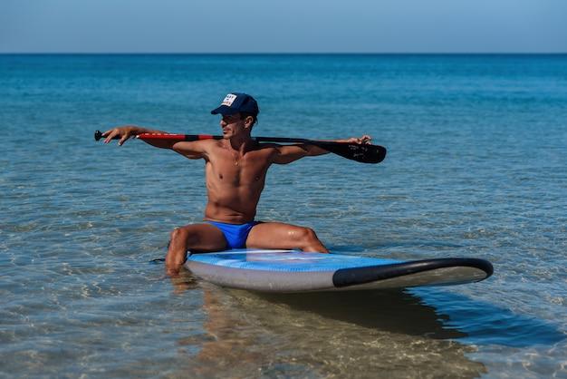Homem desportivo bronzeado em um boné senta-se em sua prancha de surf na água segurando pelas mãos um remo atrás da cabeça e olha para a água.