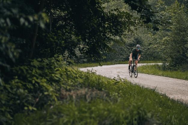 Homem desportivo com capacete e óculos a andar de bicicleta na natureza