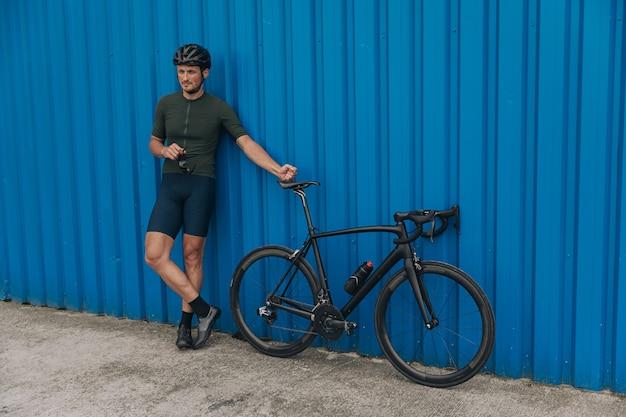 Homem desportivo com capacete perto de uma bicicleta preta ao ar livre