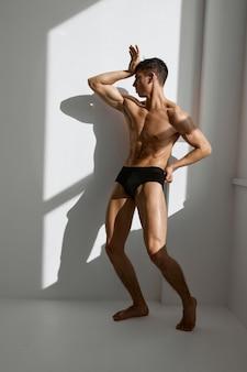 Homem desportivo com corpo nu e atarracado de calcinha preta posando perto da janela