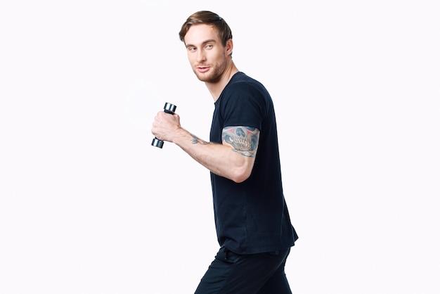 Homem desportivo com halteres em fundo branco, sua tatuagem no braço camiseta preta vista recortada