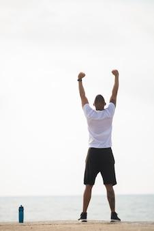 Homem desportivo contemplando a paisagem marinha durante o exercício