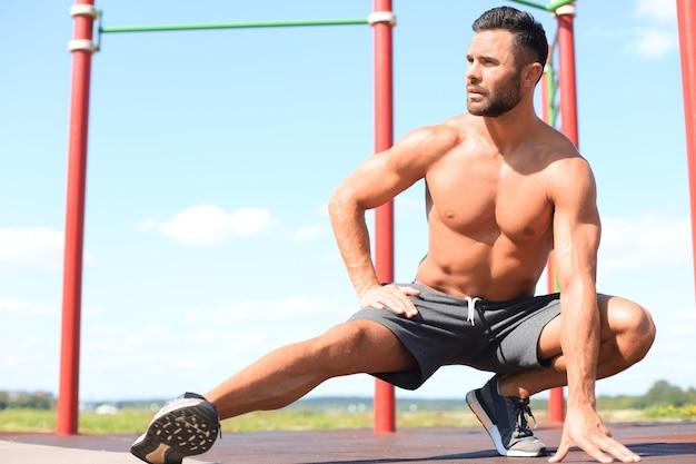 Homem desportivo, fazendo exercícios de alongamento para as pernas ao ar livre.
