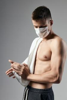 Homem desportivo máscara médica toalha nos ombros treino de fisiculturista