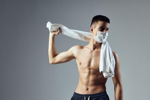 Homem desportivo máscara médica toalha sobre ombros fisiculturista