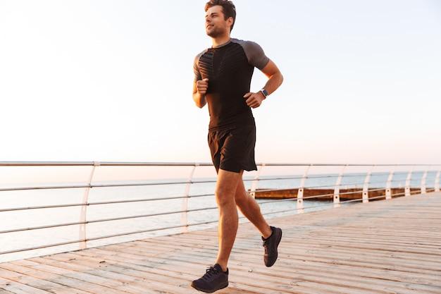 Homem desportivo musculoso de bermuda e camiseta correndo ao longo do cais ou calçadão à beira-mar, durante o nascer do sol