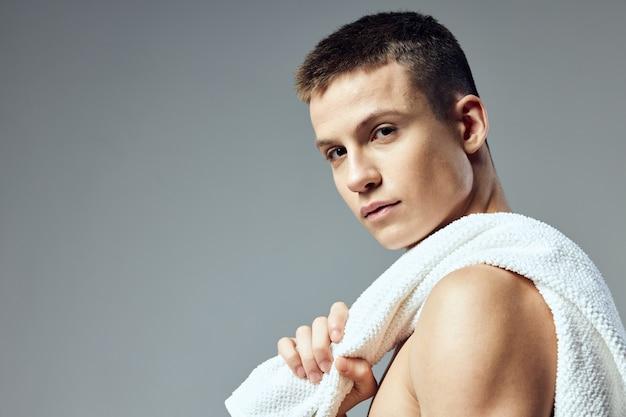Homem desportivo no corpo nu com uma toalha em close-up de mãos. foto de alta qualidade