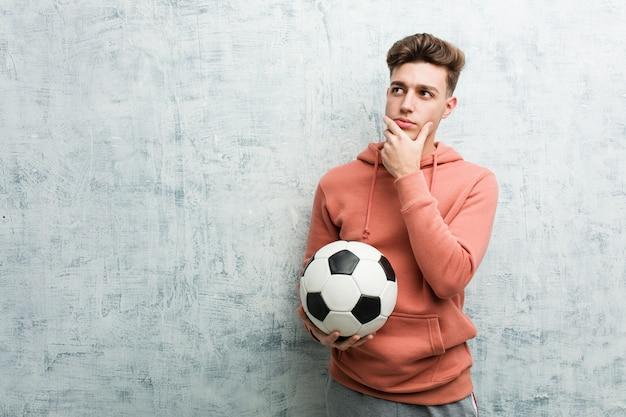 Homem desportivo novo que guarda uma bola de futebol que olha lateralmente com expressão duvidosa e cética.