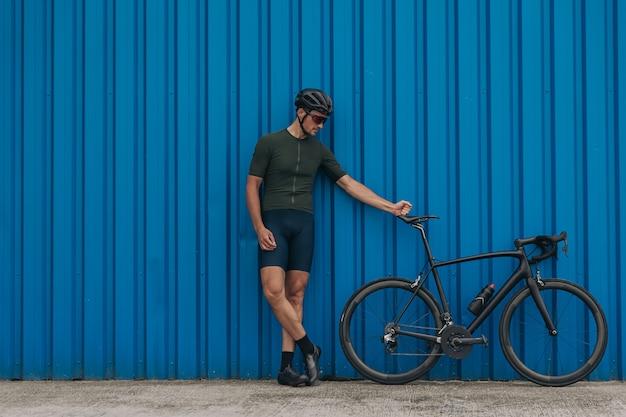 Homem desportivo posando perto de uma parede azul com uma bicicleta esportiva