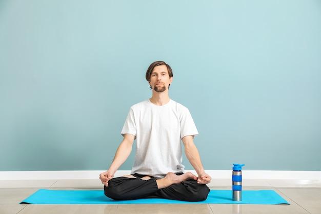 Homem desportivo praticando ioga em ambientes fechados