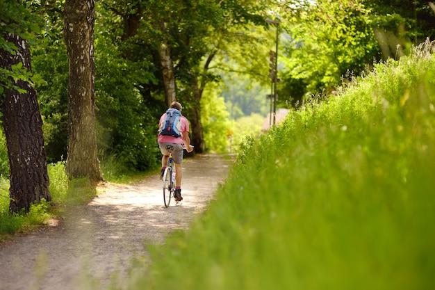 Homem desportivo que dá um ciclo no parque ensolarado no dia de verão quente. suíça, europa
