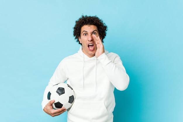 Homem desportivo segurando uma bola de futebol, gritando animado para a frente.