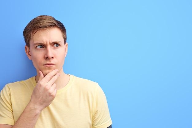 Homem desvia o olhar e pensa com uma cara séria, homem atento segurando o queixo com a mão, parado em contemplação isolado sobre fundo azul