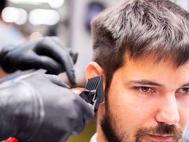 Homem desviando o olhar e cortando o cabelo